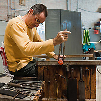 "VENICE, ITALY - DECEMBER 14:  Marino Santi, master ""maestro"" glass maker at Eugenio Ferri & C. in Murano makes glass Christmas baubles on December 14, 2010 in Venice, Italy. The production of glass baubles is an highly skilled process,with a variety of styles, often with the inclusion of gold and silver foil."