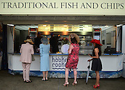 © London News Pictures. 20/06/2013. Ascot, UK. People queue for fish and chips at a food concession. Ladies Day on day three of Royal Ascot at Ascot racecourse in Berkshire, on June 20, 2013. The 5 day showcase event, which is one of the highlights of the racing calendar, has been held at the famous Berkshire course since 1711 and tradition is a hallmark of the meeting. Top hats and tails remain compulsory in parts of the course.  Photo credit : Stephen Simpson/LNP