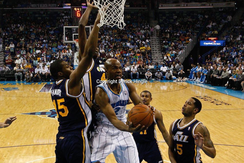 April 11, 2011; New Orleans, LA, USA; New Orleans Hornets point guard Jarrett Jack (2) shoots over Utah Jazz power forward Derrick Favors (15) and small forward C.J. Miles (34) during the first half at the New Orleans Arena.  Mandatory Credit: Derick E. Hingle