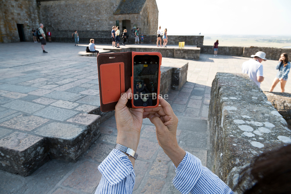 photographing with the mobile phone by the church entrance on Mont Saint Michel in France