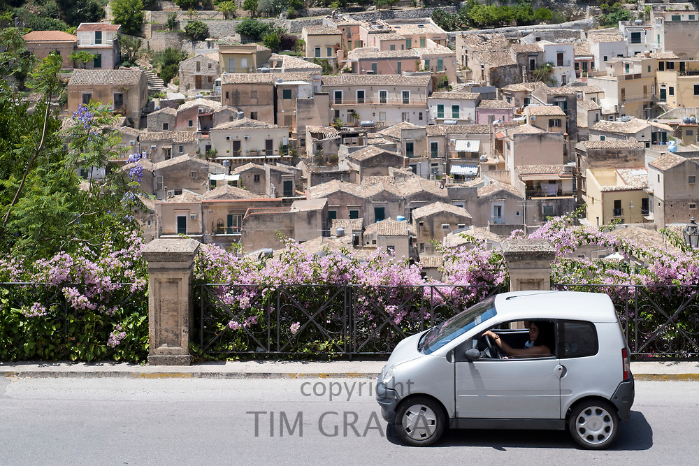 Compact white small city car in the hill city of Modica Alta famous for its Baroque architecture, South East Sicily, Italy