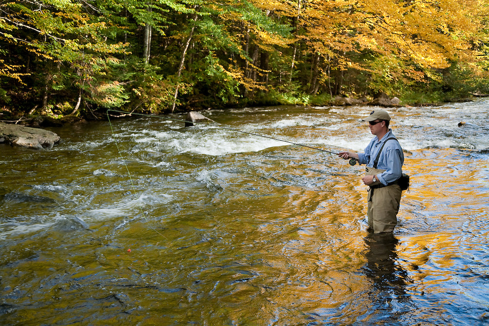 Male angler nymphing while fly fishing for trout on the upper Connecticut River in northern New Hampshire.