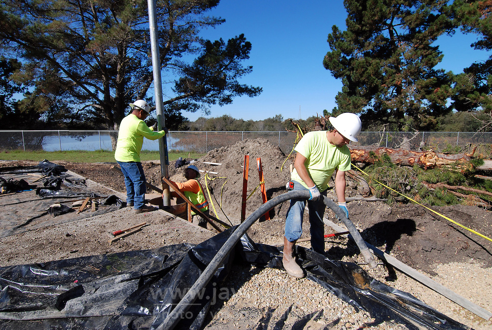 The support pole for the first basketball hoop is held in place as crew members prepare to pour concrete around it on November 12th, 2015 at the Acosta Plaza Recreation Area in east Salinas, CA.