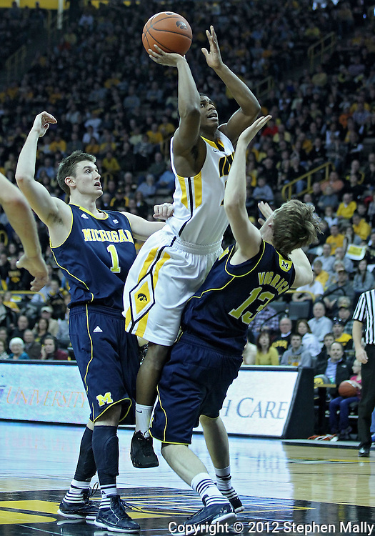 January 14, 2011: Iowa Hawkeyes guard Bryce Cartwright (24) puts up a shot over Michigan Wolverines guard Matt Vogrich (13) during the NCAA basketball game between the Michigan Wolverines and the Iowa Hawkeyes at Carver-Hawkeye Arena in Iowa City, Iowa on Saturday, January 14, 2011. Iowa defeated Michigan 75-59.