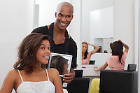 Hairdresser holding a mirror behind young woman