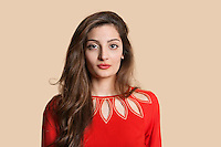 Portrait of beautiful young woman in red over colored background