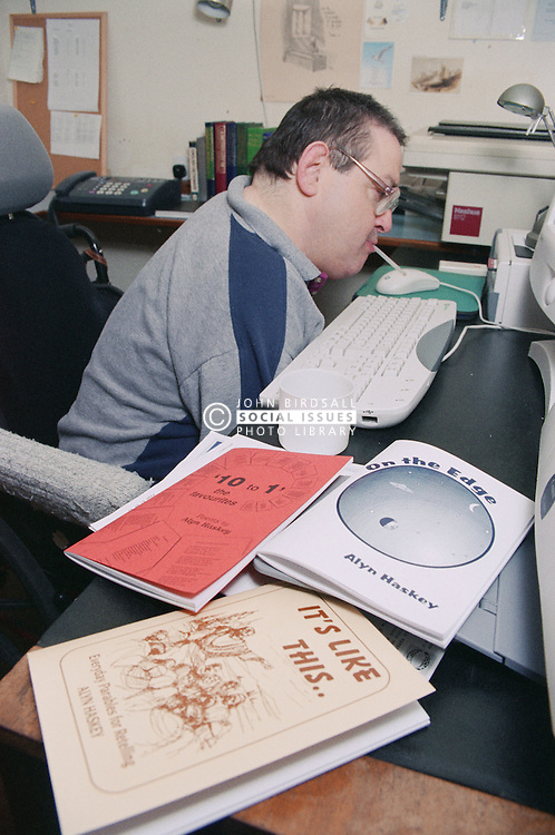Man with Cerebral Palsy sitting at desk in office using tool to type on computer keyboard,
