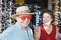 Senior couple trying on sunglasses, smiling