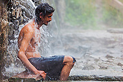 A man washes himself in the hot natural spring water before going in the pool at parvati valley in Kullu, Himachal Pradesh, India
