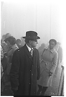 Man with hat and coat walking in smoke near a fire, Oxford street, London street photography in 1982. Tri-X