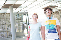 Smiling couple looking away while standing in city