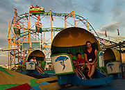 Fairgoers enjoy the tilt-a-whirl and the crazy cat coster Wednesday evening in the Midway at the Nebraska State Fair in Grand Island. (Independent/Matt Dixon)