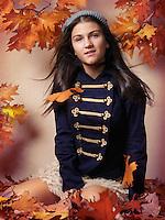 Teenage girl sitting on fallen autumn leaves artistic fall fashion portrait