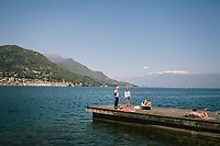 SALÒ, ITALY - 20 APRIL 2018: People are seen here sunbathing and relaxing on a pier on Lake Garda in Salò, Italy, on April 20th 2018.<br /> <br /> Lake Garda is the largest lake in Italy. It is a popular holiday location located in northern Italy, about halfway between Brescia and Verona, and between Venice and Milan on the edge of the Dolomites. The lake and its shoreline are divided between the provinces of Verona (to the south-east), Brescia (south-west), and Trentino (north).
