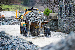 © Licensed to London News Pictures. 23/12/2015. Glenridding UK. The defiant residents of Glenridding are dredging the beck this morning ahead of more weather warnings being issued by the met office warning of 80mph winds as Storm Eva approaches. Photo credit: Andrew McCaren/LNP