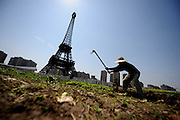 HANGZHOU, CHINA - MARCH 21: (CHINA OUT) <br /> <br /> Replica Of Paris In China<br /> <br />  A farmer works in front of a replica of The Eiffel Tower standing at 108 metres at Tianducheng residential community, also known as a knockoff of Paris, on March 21, 2014 in Hangzhou, Zhejiang Province of China. Tianducheng is developed by Zhejiang Guangsha Co. Ltd.. The construction began in 2007 with a replica of the Eiffel Tower and Parisian houses, and it is expected to be completed by 2015.  <br /> ©Exclusivepix