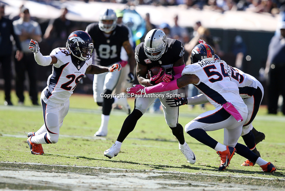 Oakland Raiders fullback Marcel Reece (45) gets tackled by Denver Broncos cornerback Bradley Roby (29), Denver Broncos inside linebacker Brandon Marshall (54), and Denver Broncos inside linebacker Danny Trevathan (59) as he catches a third quarter pass for a first down during the 2015 NFL week 5 regular season football game against the Denver Broncos on Sunday, Oct. 11, 2015 in Oakland, Calif. The Broncos won the game 16-10. (©Paul Anthony Spinelli)