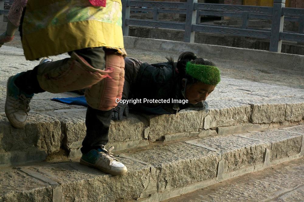 XIAHE, APRIL, 5 , 2012 : a Tibetan pilgrim prosternates at labrang monastery .