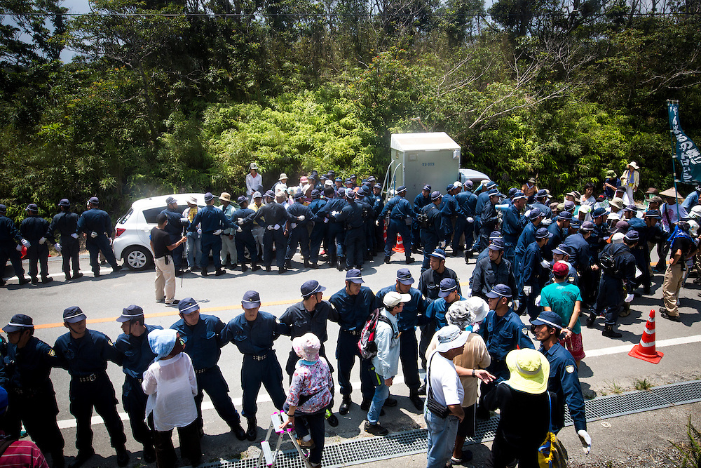 OKINAWA, JAPAN - AUGUST 19 : Anti U.S base protesters is seen being guarded by police after they staged a sit-in protest against the construction of helipads in front of the gate of U.S. military's Northern Training Area in the village of Higashi, Okinawa Prefecture, on August 19, 2016. Japanese government resume construction of total six helipads in a fragile ten million year old Yanbaru forest that is home to endemic endangered species such as the Okinawan rail and Okinawan wood pecker. (Photo by Richard Atrero de Guzman/NURPhoto)
