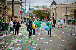 12 March 2016. New Orleans, Louisiana.<br /> Revelers walk the route following the Irish Channel St Patrick's Day parade on Magazine Street.<br /> Photo©; Charlie Varley/varleypix.com