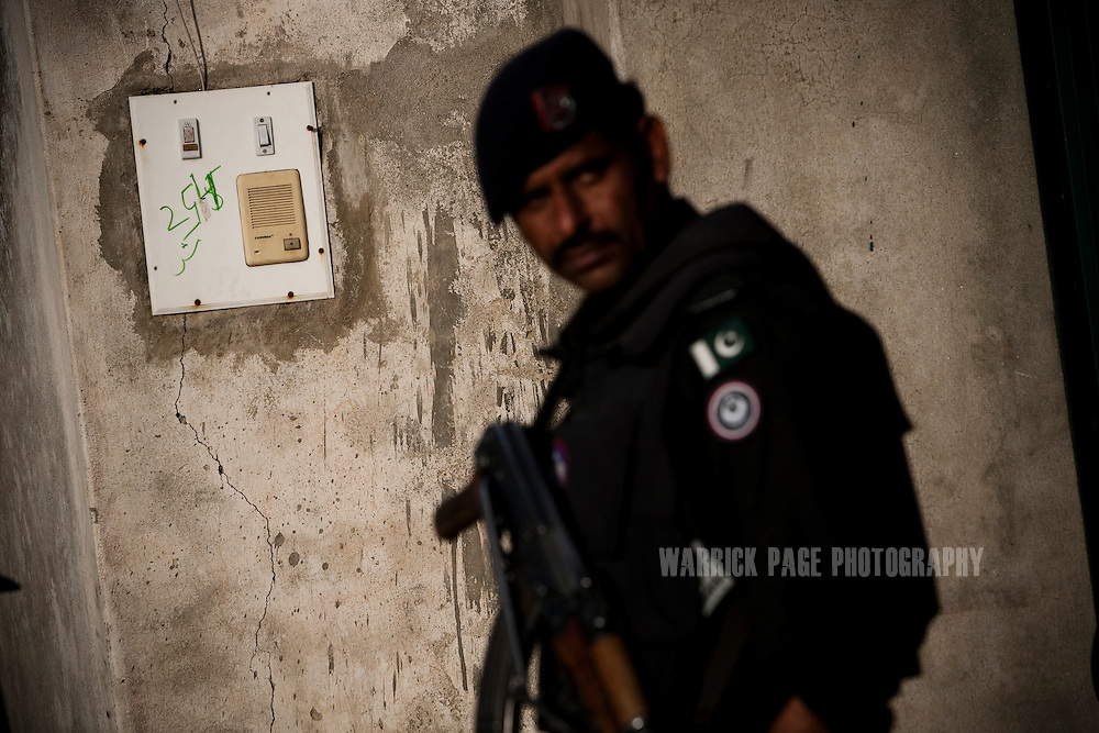 A Pakistani policeman stands next to the intercom at the entrance to the compound where Osama Bin Laden was killed in an operation by US Navy Seals, on May 4, 2011, in Abottabad, Pakistan.  The operation, code-named Operation Neptune Spear, was launched from neighbouring Afghanistan by Seal Team Six. U.S. forces took bin Laden's body to Afghanistan for identification, then dumped it the Arabian Sea. Pakistan has since been widely suspected as having prior knowledge of his whereabouts as the compound was less than a kilometre from the country's biggest military academy. Osama bin Laden was allegedly responsible for supporting the bombing of the US Embassy in Nairobi, Kenya, the attack on the USS Cole and the suicidal attacks of September 11, 2001 in the US. (Photo by Warrick Page)