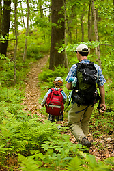 A man and his young son walk a woodland trail at Highland Farm in York, Maine.