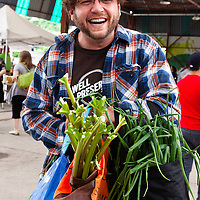 Joel MacCharles of Wellpreserved.ca  at the Brick Works farmers market with his bags of treaure: spring green garlics and rhubarb.