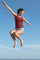 Mid adult woman jumping arms extended in mid-air