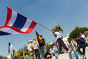 """09 DECEMBER 2013 - BANGKOK, THAILAND: Thai anti-government protestors on top of barricades in front of Government House in Bangkok. Thai Prime Minister Yingluck Shinawatra announced she would dissolve the lower house of the Parliament and call new elections in the face of ongoing anti-government protests in Bangkok. Hundreds of thousands of people flocked to Government House, the office of the Prime Minister, Monday to celebrate the collapse of the government after Yingluck made her announcement. Former Deputy Prime Minister Suthep Thaugsuban, the organizer of the protests, said the protests would continue until the """"Thaksin influence is uprooted from Thailand."""" There were no reports of violence in the protests Monday.      PHOTO BY JACK KURTZ"""
