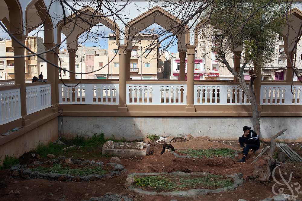 An opposition protester prays and grieves over the fresh graves of recent victims February 23, 2011 in Darna, Libya. Libya tightened its grip on the capital, tripoli, but the rest of the country appeared to be slipping further out of his control. .Slug: Libya.Credit: Scott Nelson for the New York Times