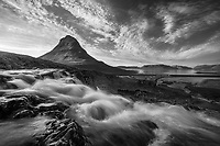 Cascade flowing past Mt Kirkjufell in western Iceland with a sky full of amazing clouds. Black & White