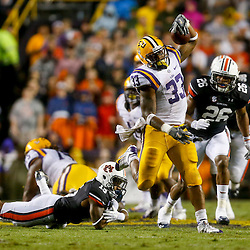Sep 21, 2013; Baton Rouge, LA, USA; LSU Tigers running back Jeremy Hill (33) breaks a tackle by Auburn Tigers defensive back Joshua Holsey (15) during the first half of a game at Tiger Stadium. Mandatory Credit: Derick E. Hingle-USA TODAY Sports