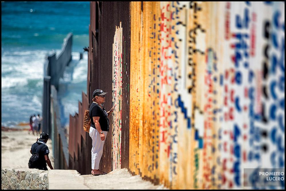 Una mujer conversa a través del muro fronterizo en las playas de Tijuana, cerca del Parque de la Amistad.. (FOTO: Prometeo Lucero)
