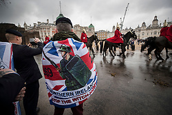 © Licensed to London News Pictures. 03/02/2018. London, UK. A former soldier wrapped in a flag depicting the troubles in Northern Ireland photographs members of  Household Cavalry as they make there way across Horse Guards Parade during a Veterans for Justice March in central London .Photo credit: Peter Macdiarmid/LNP