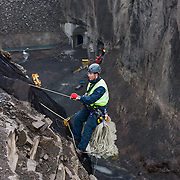 "Rope access technician Pétur Pétursson working on the removal of safety nets, in the canyon ""Hafrahvammagljúfur"", at Kárahnjúkar dam area, Iceland. Safety nets were put up to prevent rockfall onto workers, working on the lower dam."