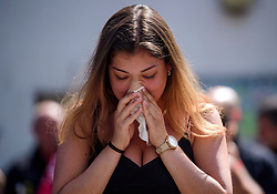 © Licensed to London News Pictures. 19/06/2017. London, UK. An emotional relative of fire victim  Jessica Urbano attends a minutes silence held near the scene of the Grenfell tower block fire. The blaze engulfed the 27-storey building killing dozens - with 34 people still in hospital, many of whom are in critical condition. Photo credit: Ben Cawthra/LNP