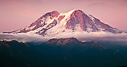 Evening alpenglow lights Mount Rainier, as seen from the southwest, in warm tones in late summer when the snow is melted to show glacial ice and bare walls. The prominent glacier in this image is the Puyallup Glacier.