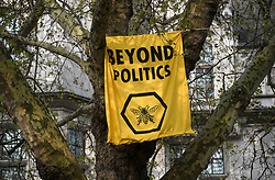 © Licensed to London News Pictures. 18/04/2019. London, UK. A banner hung by an Extinction Rebellion campaigner, high up in a tree, outside the Supreme Court on Parliament Square in London on a fourth day of protests by the group. Protesters are demanding urgent government action on climate change. Photo credit: Ben Cawthra/LNP