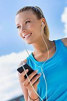 Portrait of young attractive woman standing while using and listening to music on her smartphone in park