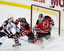 Feb 26, 2009; Newark, NJ, USA; New Jersey Devils defenseman Mike Mottau (27) and Colorado Avalanche left wing Cody McLeod (55) battle after a save by New Jersey Devils goalie Martin Brodeur (30) during the first period at the Prudential Center.