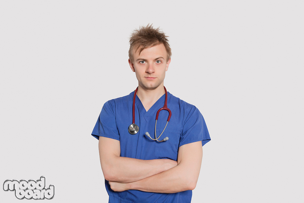 Portrait of a serious male surgeon standing with arms crossed over gray background