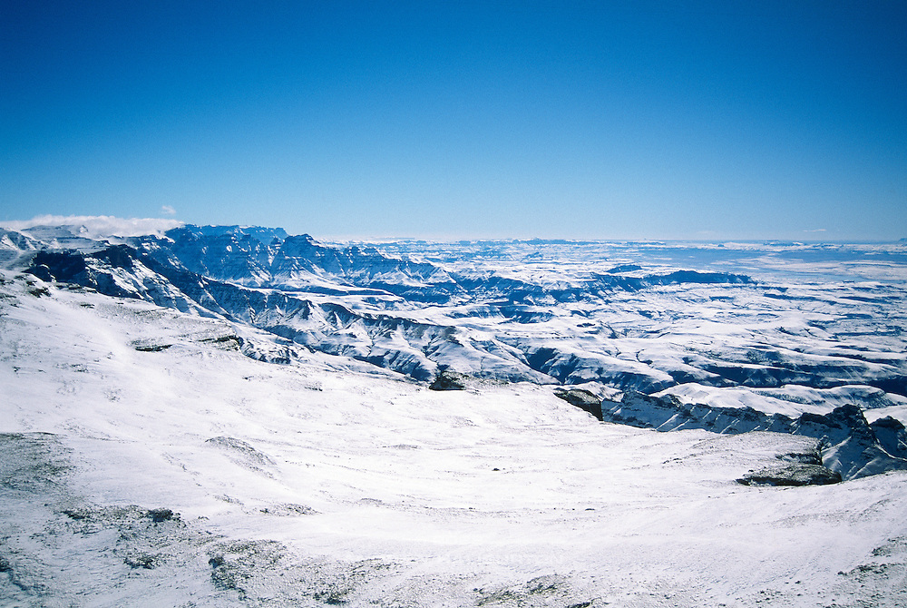 Snow covers the Mountain Kingdom of Lesotho (left) and KwaZulu-Natal Province of South Africa, as far as the eye can see, in this aerial view northward along the Drakensberg escarpment.  Photo taken at an altitude of about 3,400m (11,200 feet) from a Search and Rescue helicopter crossing the Nkosazana Ridge during the Drakensberg Snow Rescues July 7 to 11, 1996. This flight was part of an extensive 3-day search and rescue operation, coordinated jointly by SANDF 15 Squadron and the Mountain Club of South Africa (MCSA).   The operation was initiated after receiving multiple missing person reports in the wake of the record snowfalls of July 1996.  Ten helicopters were utilized in the operation: 4 Oryx, 4 BK117 and 2 Alouettes.  In total, the search tally grew to 123 known to be unaccounted for – mostly overnight backpackers.  All 123 were subsequently found, 66 were airlifted to safety, and the remainder, well prepared and in good health, chose to decline assistance.  MCSA Mountain Search and Rescue team: Andrew Haliburton, Graham Smith, Steve Cooke, Greig Stewart, Carl Fatti, Egmont Geodeke, Gavin Raubenheimer, Jeremy Farquhason, Mike Maxfield, Sean Bartleet, Ian Bailey, Dr Ian Forsyth, George Morphis, Tod Collins.  Lt-Col Eric Elphick headed up the team from 15 Squadron, comprising pilots, engineers and aircraft support.  Nikon F90, Nikon AF Nikkor 28-70/3.5-4.5D.  Fujichrome Velvia RVP 50.