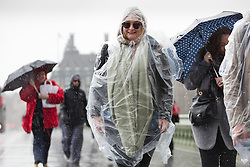 © Licensed to London News Pictures. 15/04/2016. London, UK. Tourists are caught in heavy rain showers on Westmister Bridge, central London during wet and windy weather today. Photo credit : Vickie Flores/LNP