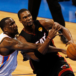 Jun 14, 2012; Oklahoma City, OK, USA;  Miami Heat power forward Chris Bosh (1) drives to the basket as Oklahoma City Thunder center Kendrick Perkins (5) defends during the first quarter of game two in the 2012 NBA Finals at Chesapeake Energy Arena. Mandatory Credit: Derick E. Hingle-USA TODAY SPORTS