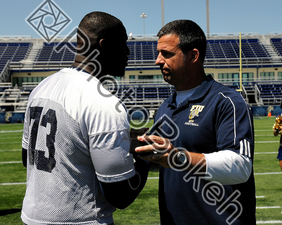 2011 April 4 - Florida International offensive lineman Stephen Bailey receiving his Sunbelt Championship ring from head coach Mario Cristobal for the victory during the Little Caesars bowl. Florida International University football offense defeated the defense in the annual Blue and Gold Spring Game, 19-10, at FIU Stadium, Miami, Florida. (Photo by: www.photobokeh.com / Alex J. Hernandez)