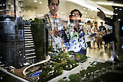 JAKARTA; SATURDAY, SEPTEMBER 20, 2014; INDONESIA ECONOMIC RISING: Visitors look at apartment maqutte as the sales officer marketing it in a mall in Jakarta, Indonesia, on Saturday, September 20, 2014. According to Asian Development Bank's 2014 report, Indonesia economy growth potential is in creative industry after for years relies heavily on natural resources such as mineral mining and palm oil. By the presidency of Joko Widodo, as a product of the third people election after the People Power Revolution in 1998, Indonesia is more confident in the economy growth and optimistic to become equal in quality to Brazil and China's economy growth. The emerging of Indonesia economy for the last one and a half decade after the end of Suharto's Dictatorship has been in significant way, the per capita growth has reached 400% under Susilo Bambang Yudhoyono presidency. Indonesia is home for 74 million of middle class as estimated by Boston Consulting Group, and  will double in 2020.