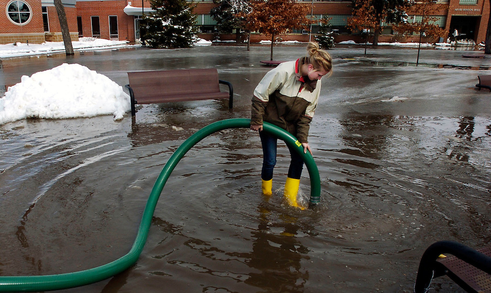 A volunteer works to pump water out of the Oak Grove Lutheran School in Fargo, N.D. The Red River breached a dike, causing the campus to flood.