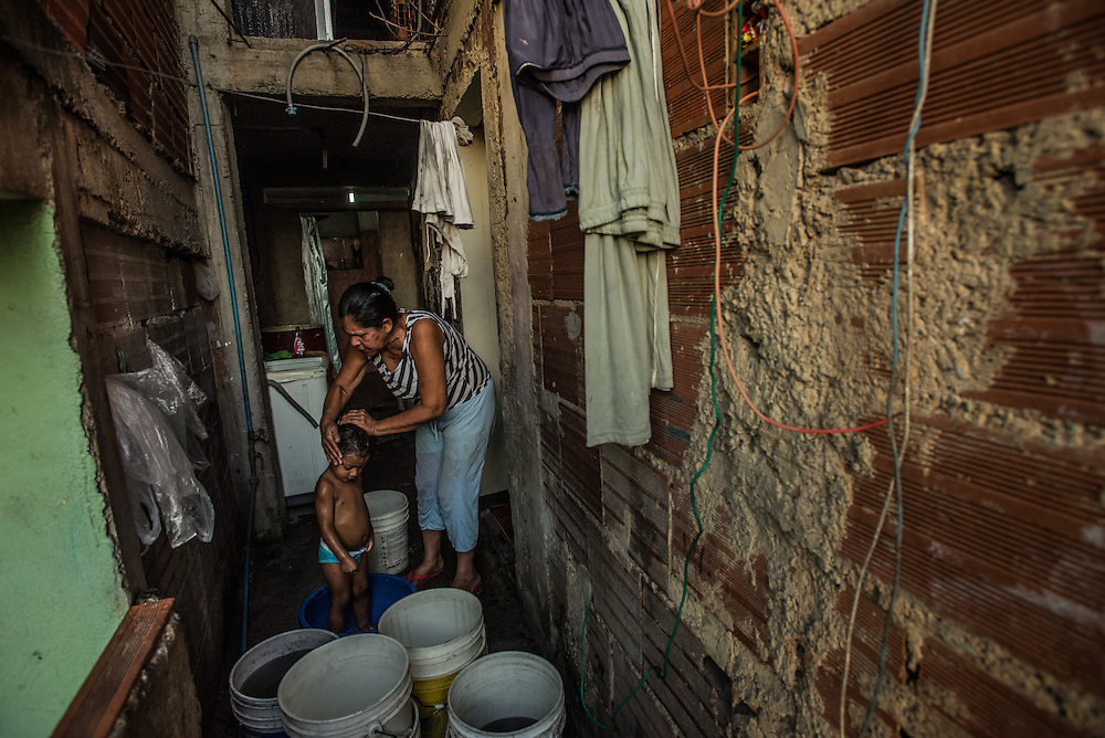 CARACAS, VENEZUELA - MAY 19, 2016: Omaira Hernandez, 53, bathes her two year old granddaughter, Isabella using buckets of water she filled at a nearby well, because the government has not provided running water to her home in over five months.  Mrs. Hernandez bathes her granddaughter in a large bucket so that she can later recycle the dirty water and use it to flush the family's toilet. Despite having the largest known oil reserves in the world, the Venezuelan government is having difficulties providing basic services like electricity and running water. They are currently rationing both. Most emblematic has been perhaps one of the most desperate measures ever by a government to save electricity: A shut down of nearly all government buildings to all but two (part-time) days each week. Government employees in Venezuela only go to work now on Mondays and Tuesdays.  All public schools now have a three-day weekend, taking off Fridays in order to save electricity.  PHOTO: Meridith Kohut for The New York Times