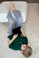 Young boy lying on rug with tablet pc