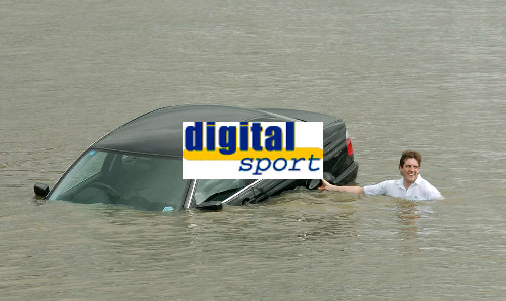 Photo: Daniel Hambury.<br />Varsity Boat Race Preview Day. 29/03/2006.<br />Oxford president Barney Williams trys to rescue a car that has been caught by the high tide.